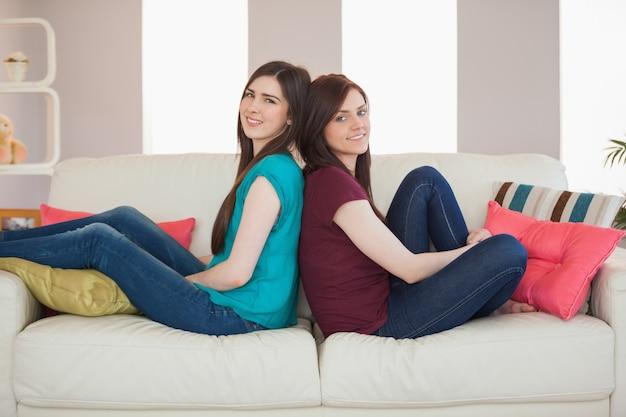 Два улыбающихся друга, сидящих спиной к спине на диване