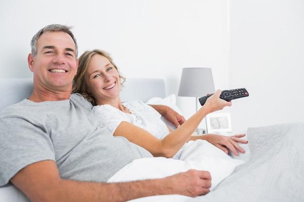 テレビを見るベッドで抱き合っている幸せなカップル
