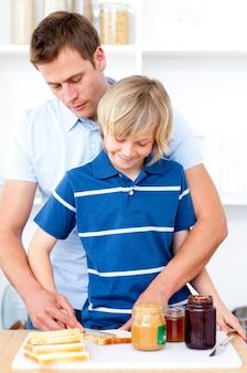 Очаровательный мальчик и его отец готовят завтрак