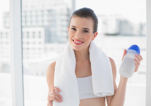 びんとタオルを持っているスポーツウェアの朗らかなフィットの茶色の髪のモデル