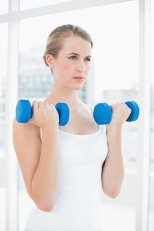 Концентрированная женщина с упражнениями с гантелями