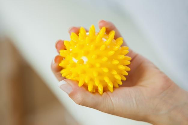 黄色のマッサージボールを保持して女性の左手のクローズアップ