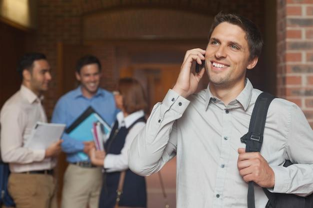 幸せな成熟した学生のスマートフォンでの電話