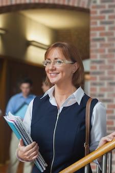 廊下でポーズをとっている幸せな女性の成熟した学生