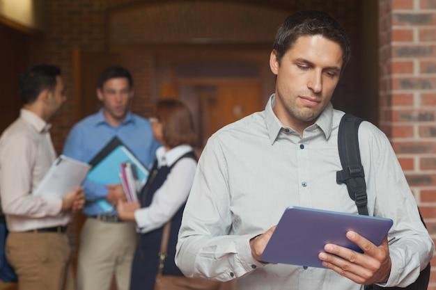 廊下に立っている彼のタブレットを保持している集中的な男性成熟した学生