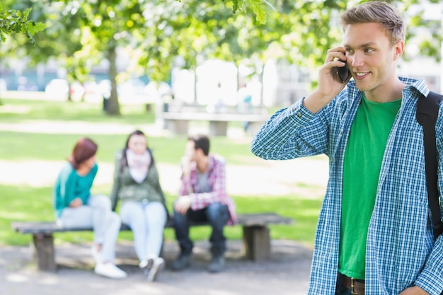Колледж мальчик, используя мобильный телефон с размытыми учениками в парке