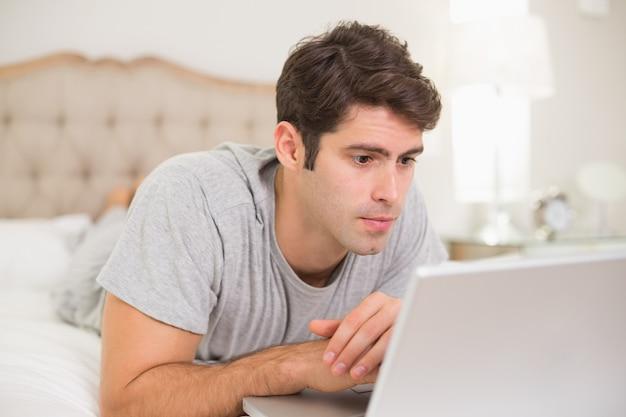 ベッドでラップトップを使用している真剣なカジュアルな若い男