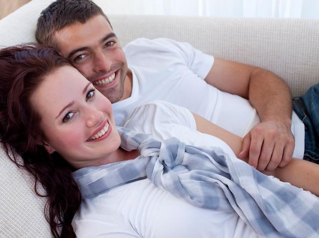 Улыбаясь пара, лежа на диване