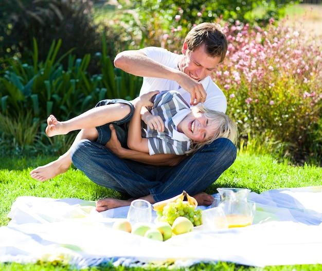 かわいい父と息子、ピクニックを楽しむ