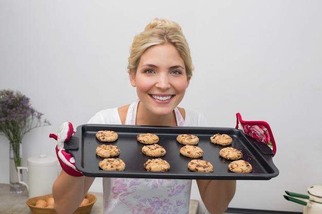キッチン、クッキーのトレイで笑顔の女性