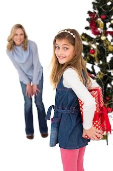 母親からクリスマスプレゼントを隠している少女