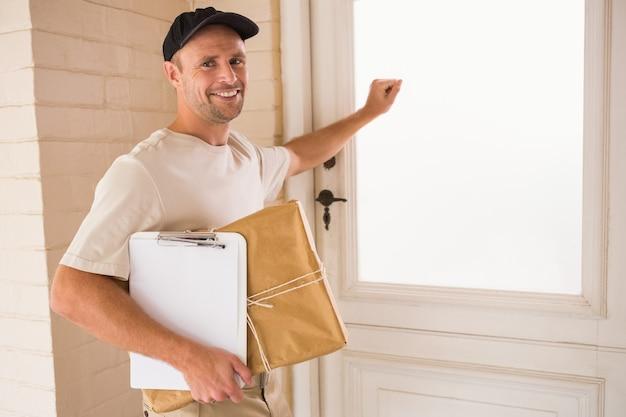 ドアでノックする笑顔のハンディーマン