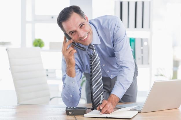 彼の机で電話を笑うビジネスマン