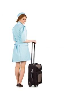 かわいいエア・ホステスがスーツケースに腰掛けている