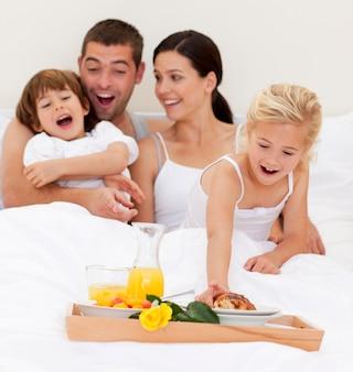 朝のベッドで朝食をしている家族