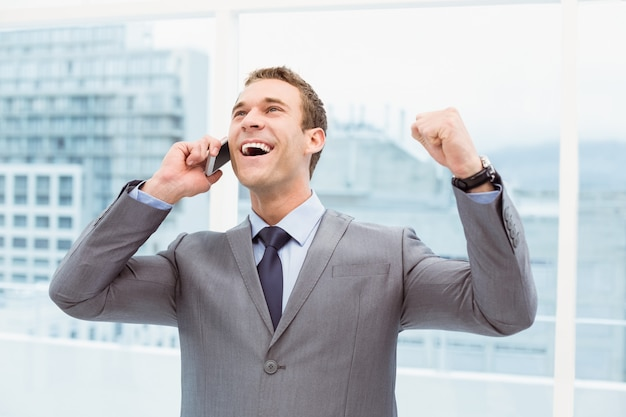 携帯電話を使用して明るいビジネスマン