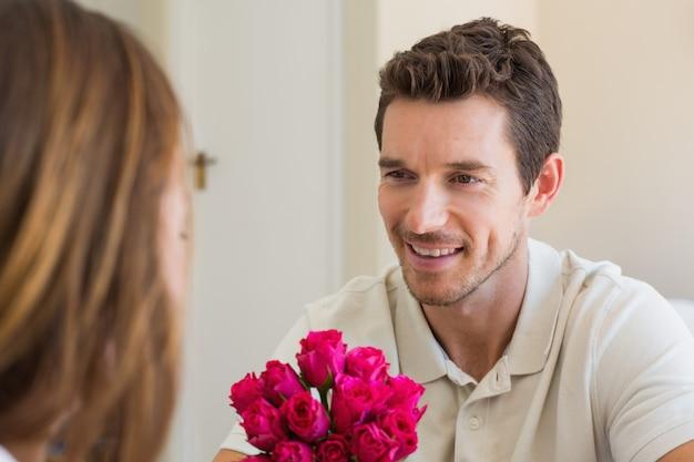 花で女性を見ている幸せな男