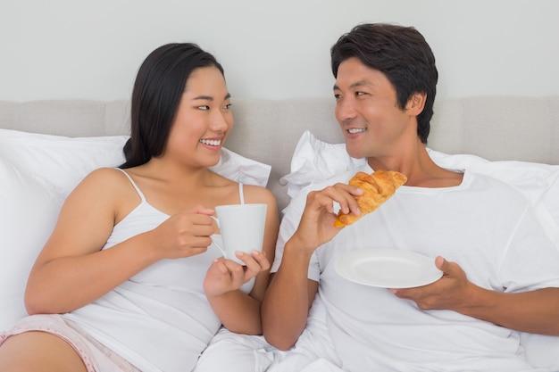 ベッドで朝食をする幸せなカップル