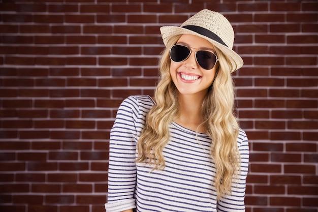 サングラスと麦わら帽子を持つゴージャスな笑顔のブロンドのヒップスター