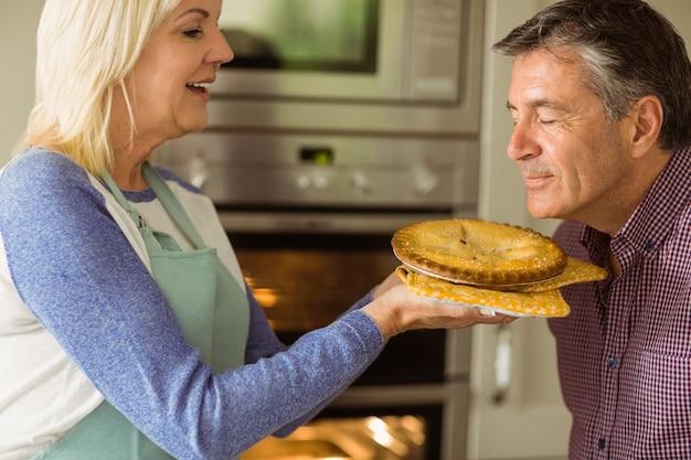 熟女のブロンド、彼女にキスする夫と新鮮なパイを保持