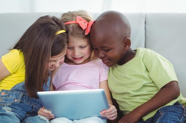 幸せな子供たちはタブレットと一緒に座って