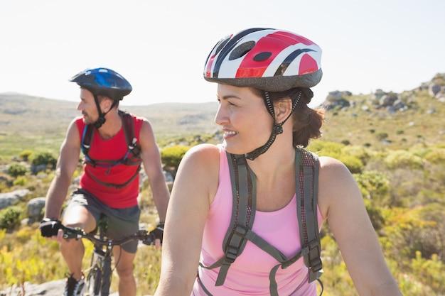 山トレイルで一緒に笑ってフィットするサイクリストカップル