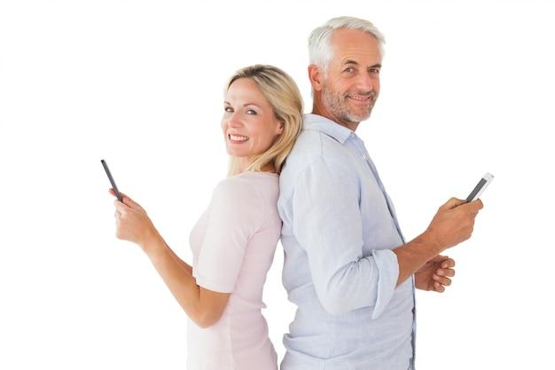 彼らのスマートフォンで幸せなカップルの文字メッセージ