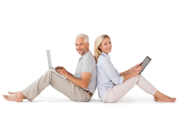 Счастливая пара, сидя с ноутбуком и планшетных пк