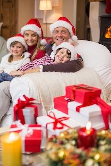 ソファの上で抱擁するサンタの帽子のお祝いの家族