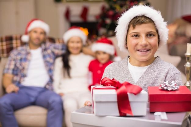 彼の家族の後ろに贈り物の山を抱いているお祝いの息子