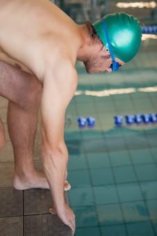 プールに潜り込む準備ができた水泳選手