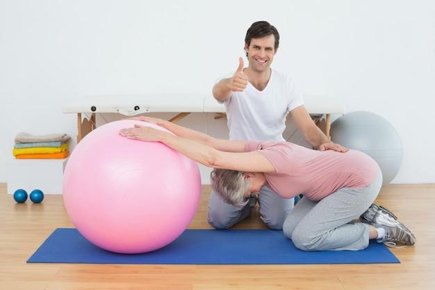 ヨガボールをしたシニアの女性が治療を指差しているセラピスト