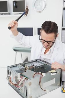 コンソールの上にハンマーを持っている怒っているコンピュータエンジニア