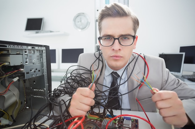 壊れたケーブルで作業しているコンピュータエンジニア