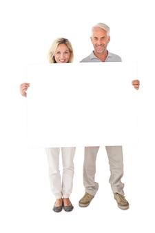 大きなポスターを持っている幸せな夫婦