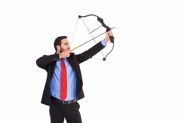 弓と矢を撮影したフォーカスされたビジネスマン