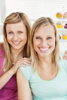 Улыбающиеся друзья пьют кофе на кухне