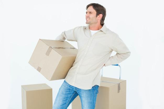 Расстроенный человек доставки с картонной коробкой, страдающей от боли в спине на белом фоне