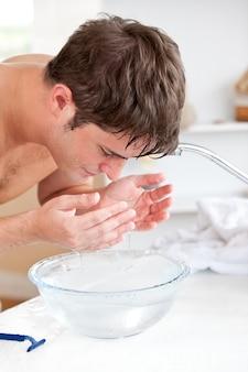 明るい男は、彼の顔に水を噴霧した後、バスルームで