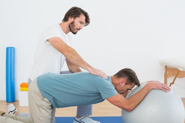 若い男を助ける理学療法士ヨガボール