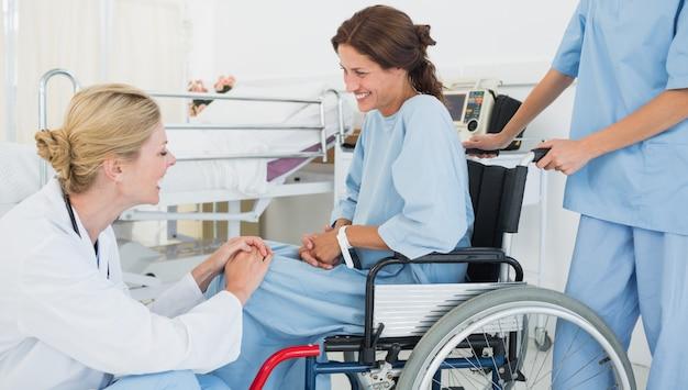 医者、病院で車椅子で患者と話す