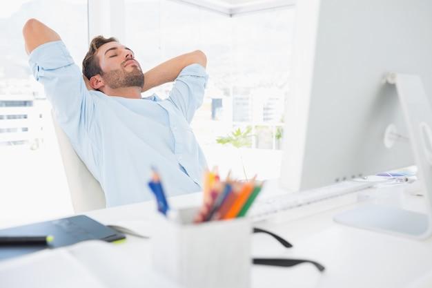 カジュアルな男は、オフィスで頭の後ろに手を置いて
