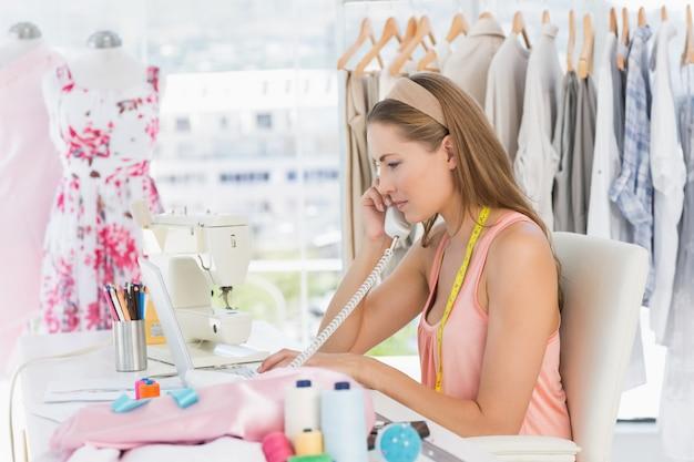 若い女性ファッションデザイナー、電話を使用して