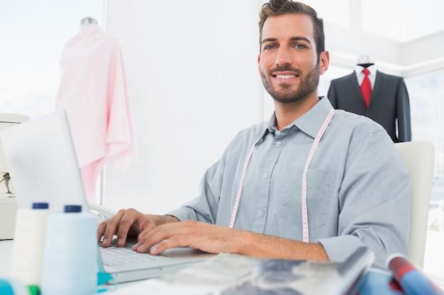 スタジオでラップトップを使用して雄のファッションデザ
