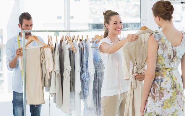 買い物客が店内で服を選ぶ手助けをする売り手