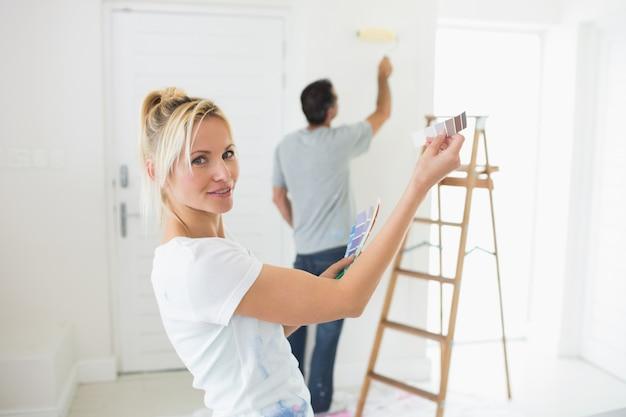 新しい家で色見本とはしごを持つカップル