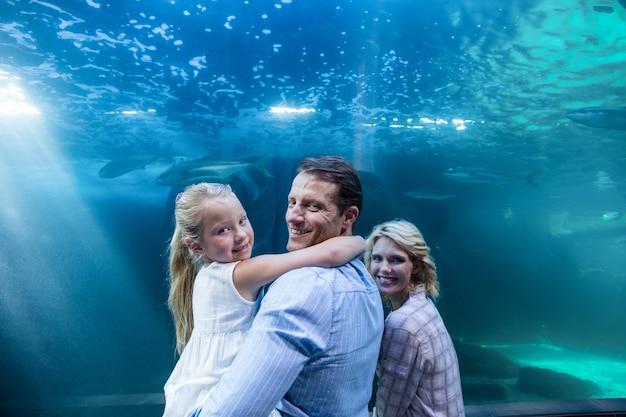 魚のタンクの後ろにカメラを見ている幸せな家族