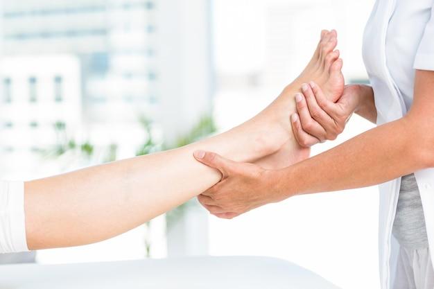 彼女の患者の足をマッサージする理学療法士