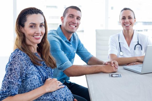 Доктор и будущие родители улыбаются в камеру