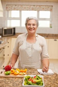 Пенсионер женщина, глядя на камеру на кухне